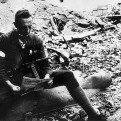 Fotografia z Powstania Warszawskiego, sierpień 1944 r.  Lektura prasy wśród gruzów. Za fotel służy plut.