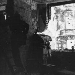 Fotografia z Powstania Warszawskiego. Stanowisko ogniowe w budynku Poselstwa Czechosłowackiego Koszykowa 18. Widoczne przejście przez otwór w ścianie do kolejnego pomieszczenia (po lewej). Fot. Marian Grabski