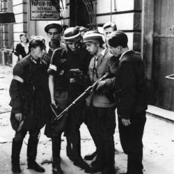 Fotografia autorstwa Eugeniusza Lokajskiego. Śródmieście Północne, ul. Sienkiewicza w pobliżu Marszałkowskiej, 1 dekada sierpnia 1944.  Powstańcy z kompanii