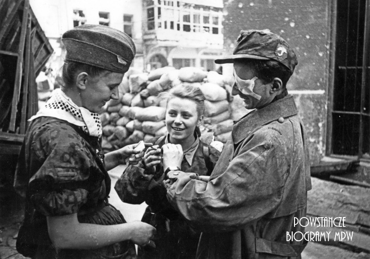"""""""Parasolarze"""" po wyjściu z kanału na ul. Wareckiej 1.09.1944 r. Zwracają uwagę: znak baonu naszyty na niemiecką czapkę polową i apaszka dziewczyny. Różnokolorowe chustki przewiązane pod szyją, w czasie walk na Starym Mieście stały się znakiem rozpoznawczym oddziałów, jednolicie ubranych w zdobyczne """"panterki"""". Każdy oddział używał chust w innym kolorze. Od lewej stoją: nierozpoznana łączniczka lub sanitariuszka, w środku """"Kama"""" (Maria Stypułkowska-Chojecka), po prawej ranny kpr. pchor. """"Krzych"""" (Krzysztof Palester - poległ 21.09.1944 na Górnym Czerniakowie). W tle widoczny Hotel """"Savoy"""" ul. Nowy Świat 58. Fot. Joachim Joachimczyk. Ze zbiorów Fototeki MPW, sygn. MPW-IK/2960"""