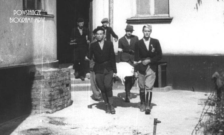 """3 sierpnia 1944. Żołnierze dywizjonu """"Jeleń"""" na Mokotowie podczas przenoszenia ciała poległego ppor. Stanisława Jenike """"Hańskiego"""". Od lewej: ułan Wiktor Wcisło """"Kmita"""", ułan pchor. Józef Jezierski """"Aksak"""" (w berecie), kpr. pchor. Andrzej Sroczyński """"Nowak"""", st. ułan pchor. Paweł Mańkowski """"Rapier"""", st. ułan pchor. Władysław Grabiński """"Pilawa"""". Archiwum Fotograficzne Stefana Bałuka"""