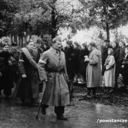 Zdjęcie przedstawiające Powstańców idących do niewoli. Na czele kolumny Powstańców  z laską, w furażerce i z wąsikiem  Jerzy Otto, ps.