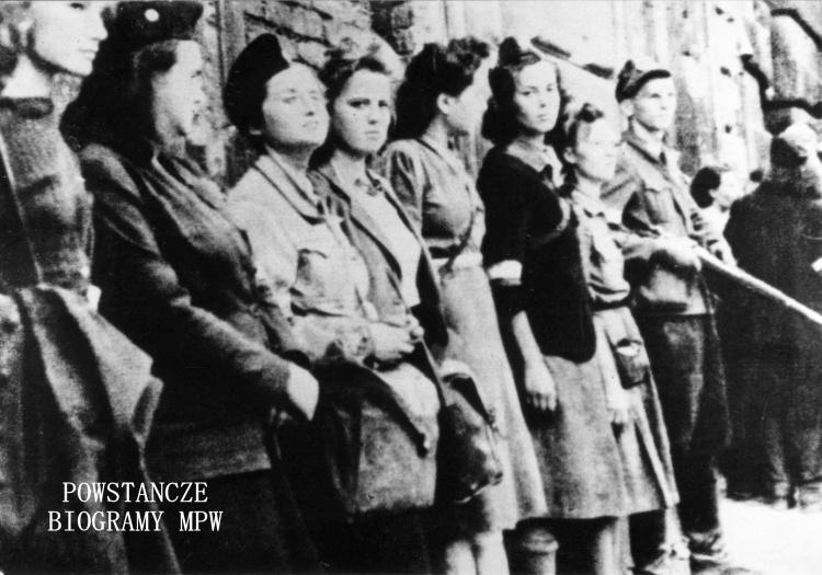 """Powstanie Warszawskie - Śródmieście Północ. Dziewczęta z 3 kompanii batalionu  """"Kiliński"""": stoją od lewej: Maria Dynkowska """"Olsza"""",  Krystyna Kamińska """"Ksenia"""" (poległa 6.09.1944 na ul. Górskiego 2), Barbara Szczepińska (Zowczak) """"Lidia"""", Natalia Koszewska """"Iza"""" (poległa 6.09.1944 na ul. Górskiego 2),  Maria Kudelska """"Marysia"""",  Krystyna Szeronos """"Ania"""", Danuta Dziama """"Hela"""". Fot. Zbigniew Zowczak """"Karo"""". Ze zbiorów Muzeum Powstania Warszawskiego, sygn. MPW-IP/2135"""