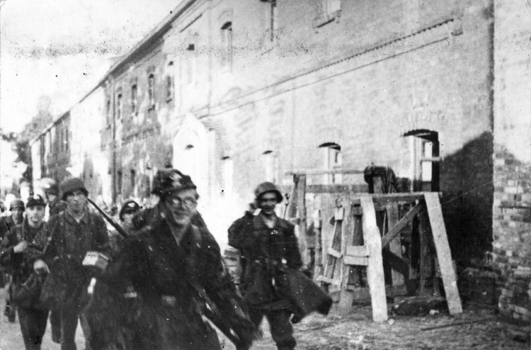 """Powstanie Warszawskie - Wola. Porucznik """"Halinka"""" prowadzi pluton """"Topolnickiego"""" przez podwórze  """"Twierdzy"""" - szkoły przy ul Okopowej 55a. Zdjęcie wykonano pomiędzy 3 a 7 sierpnia 1944 r. Fot. udostępnił  p. Bogusław Kostka"""