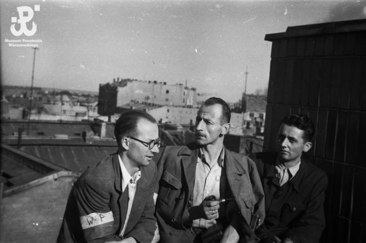 """Śródmieście Południowe, sierpień - wrzesień 1944 r. Posterunek na dachu kamienicy przy ul. Marszałkowskiej 56 - oczekiwanie na zrzuty. W środku siedzi Wacław Loth """"Kupiec"""". Ujęcie w kierunku wschodnim. W tle widoczna bryła masywnej kamienicy Mokotowska 45, róg Piusa XI nr 11 i 11B. Ze zbiorów Fototeki MPW sygn. MPW-IN/4623"""