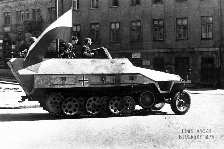 """Transporter opancerzony Sdkfz 251/1 Ausf D. """"Jaś"""" (""""Szary Wilk"""") użyty przez Powstańców 23 sierpnia 1944 do szturmu na opanowany przez Niemców Uniwersytet Warszawski. Atak ten nie powiódł się, a dowódca transportera, plut. pchor. Adam Dewitz (na zdjęciu z pistoletem maszynowym MP-40) poległ. Po jego śmierci, transporter noszący do tej pory imię """"Jaś"""" został przemianowany na """"Szarego Wilka"""". Fot. Sylwester """"Kris"""" Braun."""