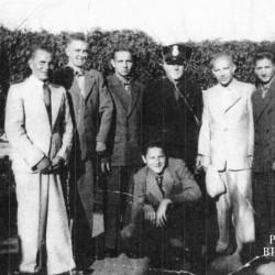 Fotografia wykonana w lipcu-sierpniu 1945 r. w Ystad (Szwecja). Opis zdjęcia: <i> Kwarantanna w Hali Sportowej </i>. Stoją od lewej: NN, NN, Jerzy Walerych, policjant szwedzki (NN), Zygmunt Szczutkowski, Piotr Łubieński i Julian Myśliwiec. Klęczy NN. Fot.  z archiwum  Piotra Łubieńskiego.