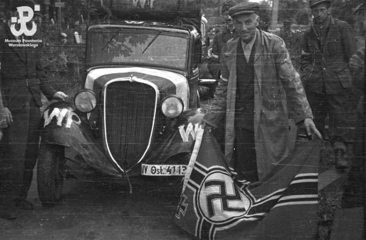 """Wola, 2 sierpnia 1944 r. Dowódca Batalionu """"Pięść"""" - mjr Alfons Kotowski """"Okoń"""" demonstruje zdobytą hitlerowską flagę na terenie cmentarza ewangelicko-augsburskiego. Zdjęcie autorstwa Stefana Bałuka, ze zbiorów Fototeki MPW , sygnatura<a href="""" http://www.1944.pl/galerie/fototeka/foto/7902/autor/126""""> MPW-IS/128</a>"""