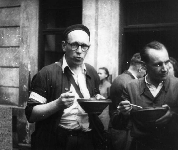 Śródmieście Północne. Powstańcza stołówka przy ul. Szpitalnej 8. Operator Henryk Vlassak (po lewej) podczas spożywania posiłku, prawdopodobnie sierpień 1944 r. Ze zbiorów Muzeum Powstania warszawskiego.