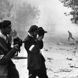 4 września 1944 roku: Śródmieście Północne. Operatorzy filmowi Stefan Bagiński (po lewej) i Antoni Wawrzyniak (po prawej) przy pracy na skrzyżowaniu ul. Jasnej i Moniuszki (w tle). Na drugim planie po lewej widoczny fragment gmachu Filharmonii. Zdjęcie autorstwa Sylwestra