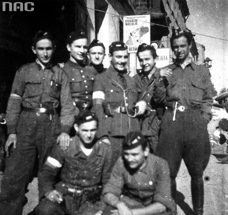 """Wrzesień 1944 roku: żołnierze III plutonu kompanii szturmowej batalionu """"Kiliński"""" na ulicy Grzybowskiej. Modest Abratański """"Szatan""""stoi pierwszy po prawej. Pozostałe osoby na zdjęciu:od lewej - Stefan Rek """"Granit"""", Wojciech L. Strzyżewski """"Jontek"""", Zbigniew Szostkiewicz """"Bohun"""", Wojciech Wyczański """"Wojczan"""", strz. Zdzisław Jarzęcki """"Witold"""", poniżej: Tadeusz Załucki """"Józków"""", Stanisław Wielgo """"Karcz"""". Archiwum Fotograficzne Stefana Bałuka, zbiory NAC, sygn. 37-1530-1"""