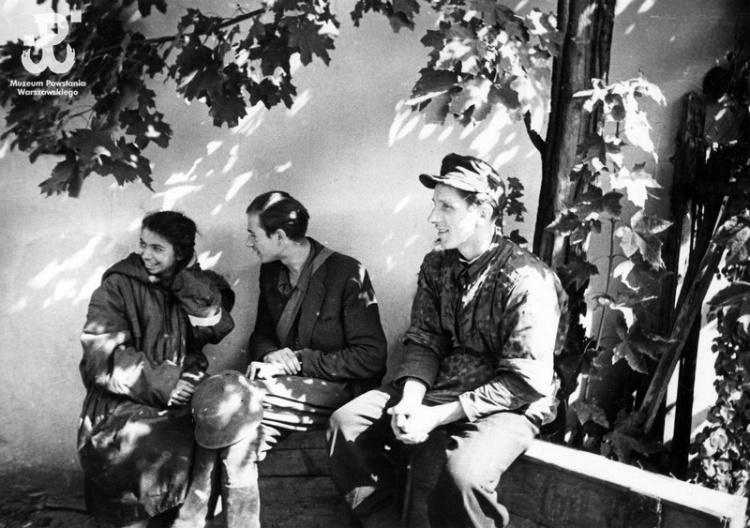 """Zdjęcie wykonane 2 IX 1944 r., tuż po ewakuacji resztek batalionu kanałami ze Starego Miasta do Śródmieścia. Od lewej siedzą: sanitariuszka """"Iza"""" - Izabela Łucja Wilbik, strz. """"Ulatowski"""" - Jan Welt i strz. """"Kowalski"""" - Tadeusz Roman. Fot. Joachim Joachimczyk ps. """"Joachim"""". Ze zbiorów MPW"""
